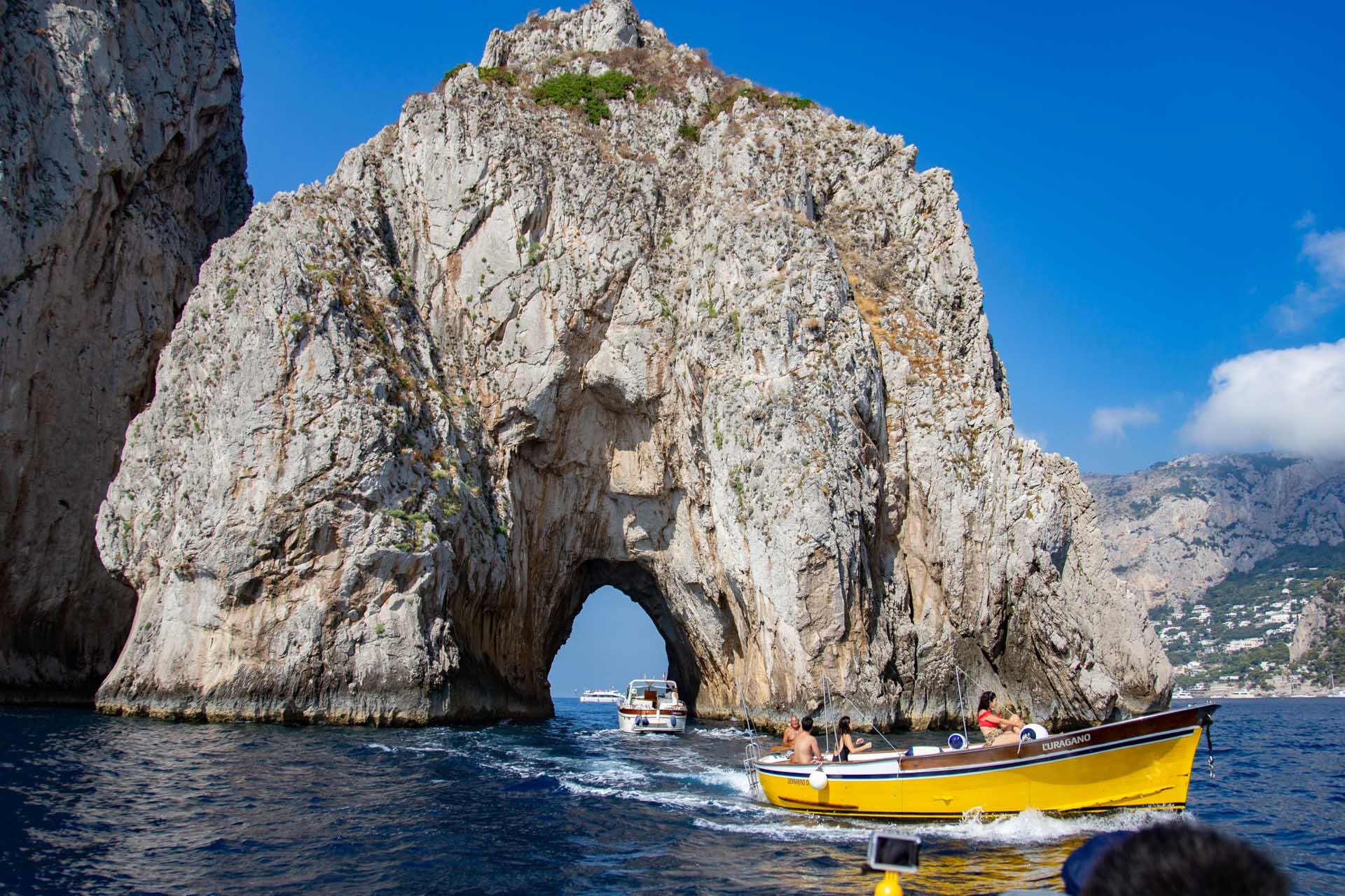 Passaggio con la barca sotto il faraglione di Capri